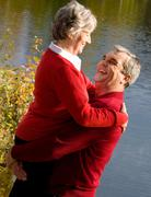 image of senior man holding his wife while spending time by the lake - stock photo