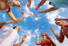 Below view of teenage friends catching ball on background of cloudy sky Stock Photos