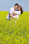 image of happy couple embracing in yellow meadow at summer - stock photo