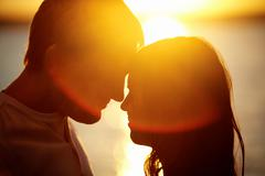 Profiles of romantic couple looking at each other on background of sunset Stock Photos