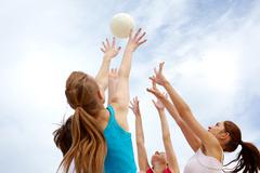Photo of teenage friends playing with ball on background of cloudy sky Stock Photos