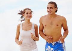 Photo of fit and healthy couple running on background of cloudy sky Stock Photos