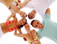 Below view of joyful teens looking at camera with smiles Stock Photos