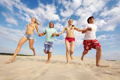 Photo of happy friends running down sandy beach on background of cloudy sky Stock Photos