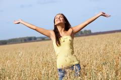 Image of joyful girl with stretched arms standing in the middle of rye field Stock Photos