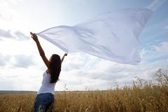 back view of charming girl raising her arms with chiffon shawl in wheat field - stock photo