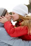 Portrait of happy couple kissing outdoors in winter Stock Photos