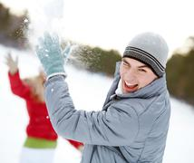 image of attractive young man laughing while under snowball bombing - stock photo