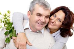 Portrait of attractive middle aged woman with rose bunch embracing her husband o Stock Photos