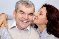 portrait of middle aged woman embracing happy man while he laughing - stock photo