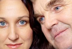 Face of middle aged woman looking at camera with man near by Stock Photos