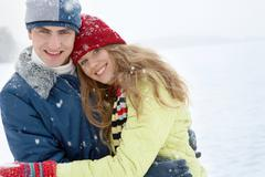 portrait of happy young family together looking at camera in winter - stock photo