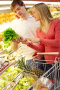 Portrait of happy couple choosing greenery in supermarket Stock Photos