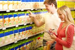 image of man taking product and woman checking her plan - stock photo