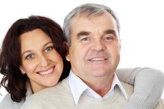 Portrait of happy mature couple looking at camera while woman embracing man Stock Photos