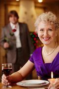 Hetki ennen kokousta: nainen odottaa hänen mies ravintolassa Kuvituskuvat