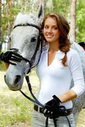 Image of happy female looking at camera with horse near by Stock Photos