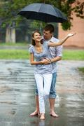 A young couple walking in the rain barefoot Stock Photos