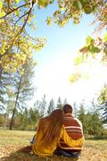 Rear view of affectionate couple relaxing outdoors in autumn Stock Photos