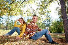 Photo of happy girl with handsome male relaxing outdoors in autumn Stock Photos