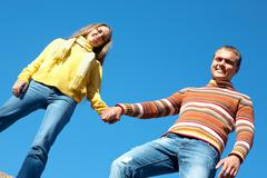 Photo of happy couple holding by hands against blue sky Stock Photos