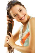 happy young woman holds her long hair and looking at camera - stock photo