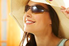 portrait of happy girl in hat looking through sunglasses - stock photo