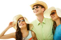 portrait of stylish man and girls in hats looking upwards through sunglasses - stock photo