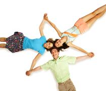 above view of three friends holding by hands in isolation - stock photo