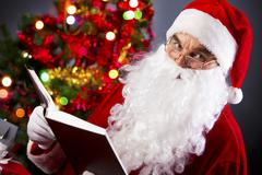santa looking at camera while reading a book - stock photo