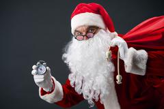 Santa looking at camera and showing face of clock Stock Photos