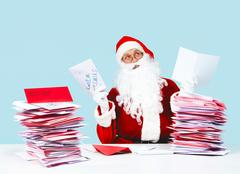 portrait of inspired santa claus holding letters and looking upwards - stock photo