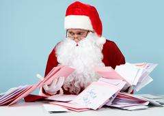 image of santa claus looking at heap of letters with terrified expression - stock photo