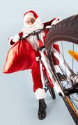 Photo of amazed santa claus with red sack on bike Stock Photos