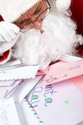 Image of santa claus in front of heap of letters reading one of them Stock Photos