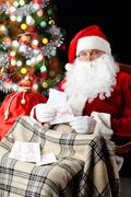 santa sitting at the christmas tree and reading christmas letters - stock photo
