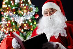 Santa sitting at the christmas tree and reading a book Stock Photos