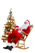 santa sitting in the armchair at the christmas tree and holding a sack isolated - stock photo