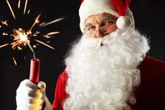 Stock Photo of portrait of santa with a burning stick of dynamite isolated on black