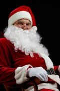 santa sitting and smiling isolated on black - stock photo