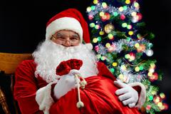santa sitting with a sack at the christmas tree - stock photo