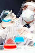 image of clinician pouring blue liquid into glass tube in laboratory - stock photo