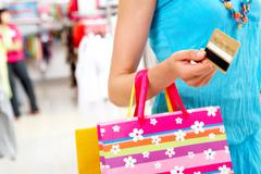 Close-up of woman holding her credit card and carring paper bag Stock Photos