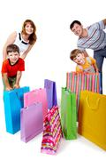 image of cheerful family members near colorful shopping bags looking at camera - stock photo