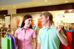portrait of pretty female and happy man looking at each other during shopping in - stock photo