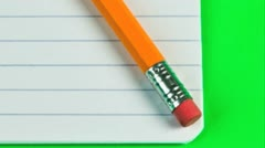 Pencil and eraser on a lined pad of paper Stock Footage