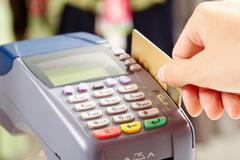 close-up of payment machine buttons with human hand holding plastic card near by - stock photo
