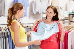 Image of pretty girl showing blue tanktop to her friend in the department store Stock Photos