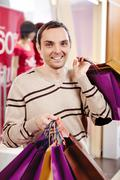 happy man with bags looking at camera with smile - stock photo