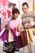 Portrait of pretty female looking at bags in man hands after shopping Stock Photos